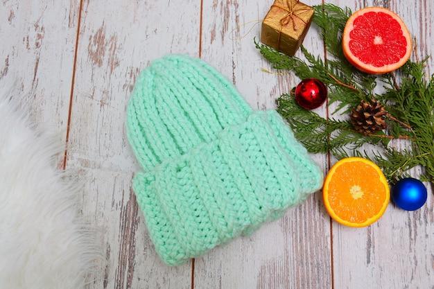 Concetto di capodanno. cappello color menta, agrumi e addobbi per l'albero di natale. sfondo in legno