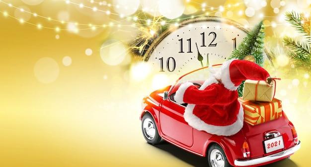 Sfondo della carta di capodanno 2021. babbo natale alla guida di un'auto rossa con scatole regalo e albero di natale su sfondo dorato con luci bokeh