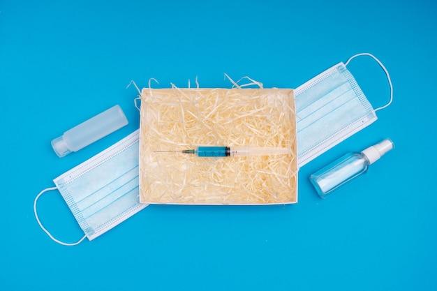 Regalo di capodanno 2020 2021. una scatola con un regalo di natale per il vaccino contro il coronavirus.