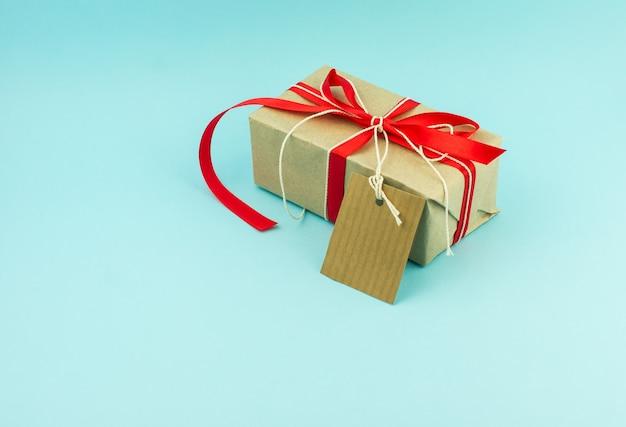Regalo di capodanno confezionato in carta kraft con nastro di raso rosso e un biglietto per le congratulazioni. sfondo blu.