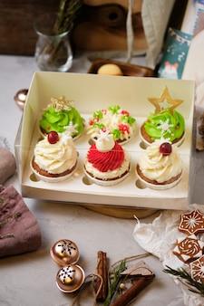Set regalo di dolci di capodanno. una scatola di cupcakes come regalo di natale. torte con crema di formaggio cremoso e ripieno di caramello alle arachidi.