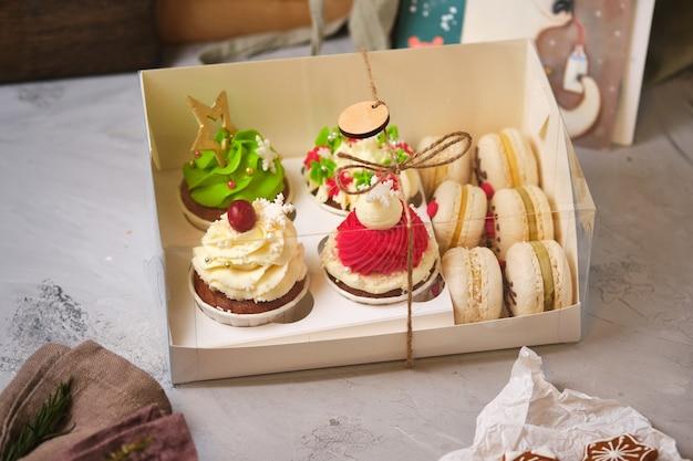 Set regalo di dolci di capodanno. una scatola di cupcakes e macarons come regalo di natale. cupcakes con crema di formaggio cremoso e ripieno di caramello alle arachidi e torte di macarons con ripieno di mandarino.