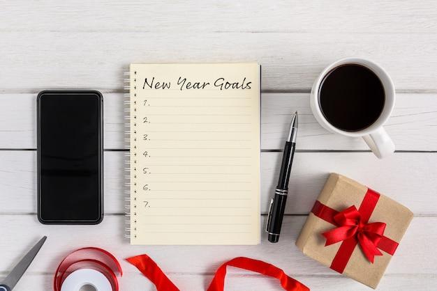 Elenco degli obiettivi di capodanno scritti su notebook con confezione regalo e smart phone, penna, caffè