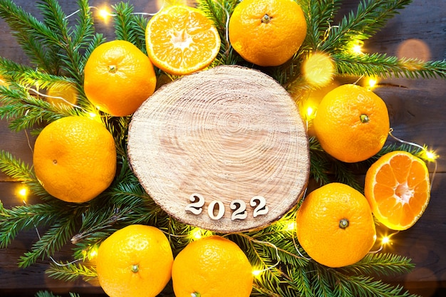 Sfondo per le vacanze di capodanno su un taglio rotondo di un albero circondato da mandarini, rami di abete vivo e ghirlande di luci dorate, con numeri in legno data 2022. aroma di agrumi, natale. spazio per il testo.