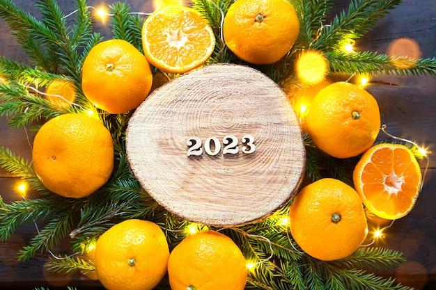 Sfondo per le vacanze di capodanno su un taglio rotondo di un albero circondato da mandarini, rami di abete vivo e ghirlande di luci dorate, con numeri in legno data 2023. aroma di agrumi, natale. spazio per il testo.