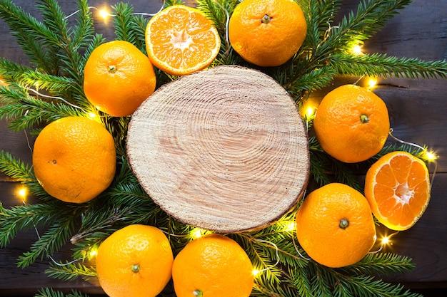 Sfondo di vacanze di capodanno sul taglio rotondo di albero circondato da mandarini, rami di abete vivo e ghirlande di luci dorate, con spazio in legno per il testo. profumo di agrumi, fettine di arancia, natale. telaio