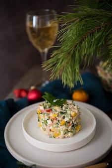 Insalata di festa di capodanno con maionese, tavola di capodanno, champagne, primo piano