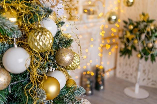 L'interno della casa di capodanno in colore oro, albero di natale con palloncini e ghirlanda