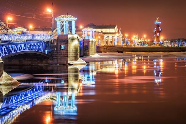 Il ponte del palazzo di capodanno a san pietroburgo e le colonne rostrale si riflettono nel fiume neva alla luce delle luci notturne