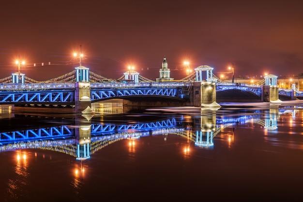 Ponte del palazzo di capodanno a san pietroburgo in una notte d'inverno e il suo riflesso nel neva