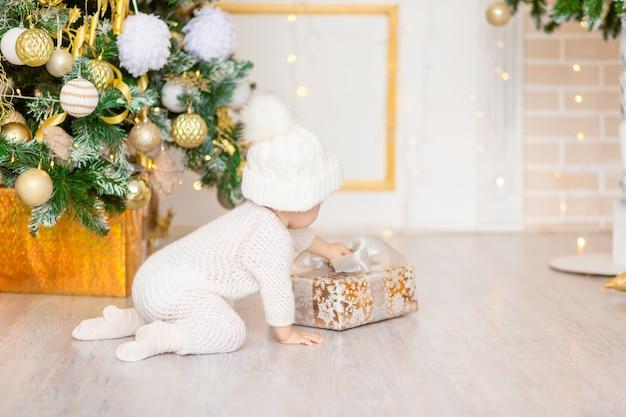 Foto di capodanno del bambino vicino all'albero di natale con un regalo
