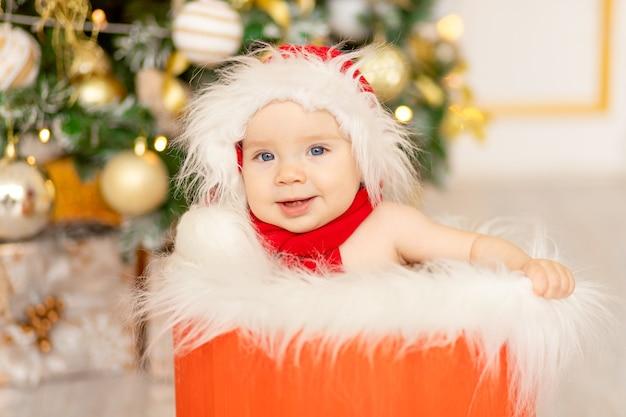 Foto di capodanno di un bambino vicino all'albero di natale con un cappello da babbo natale