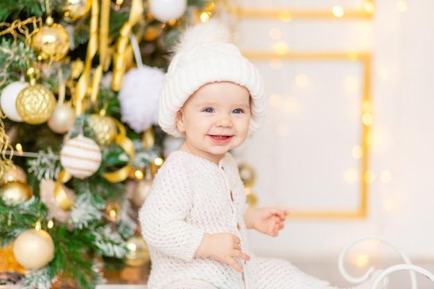 Foto di capodanno di un bambino vicino all'albero di natale in abiti bianchi invernali