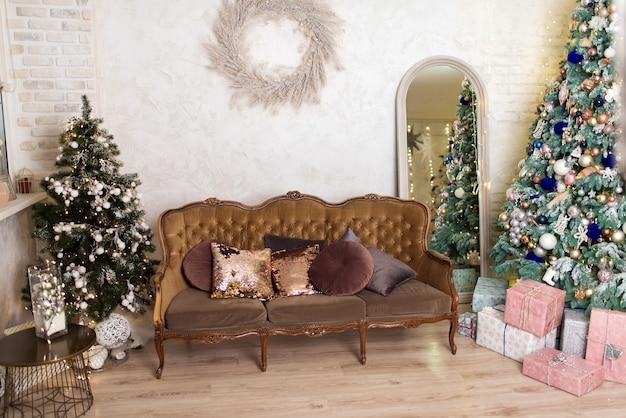 Studio fotografico di capodanno con albero di natale, addobbi e divano