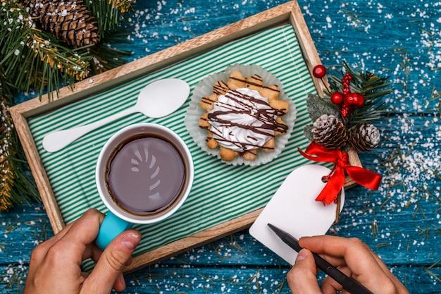 Foto di capodanno di tè con foto di candycane e torte sul tavolo con rami di abete rosso, persona che scrive desideri sulla cartolina