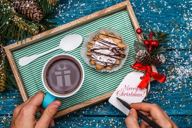 Foto di capodanno di tè con foto di regalo, torta sul tavolo con ramo di abete rosso, persona che scrive desideri sulla cartolina