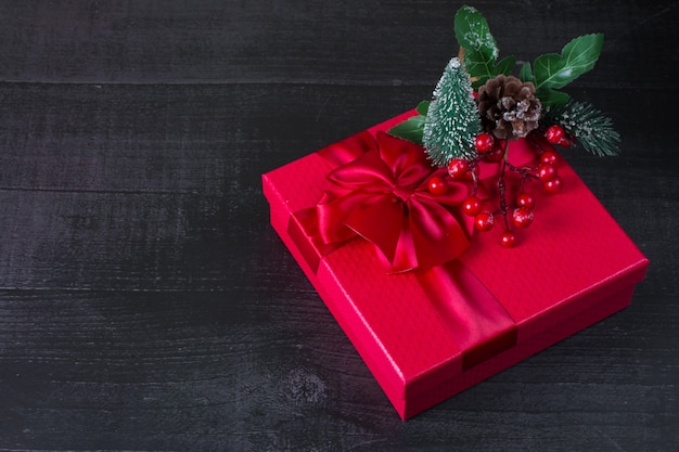 Confezione regalo rossa di capodanno. un rametto di albero di natale con frutti di bosco è un regalo di natale