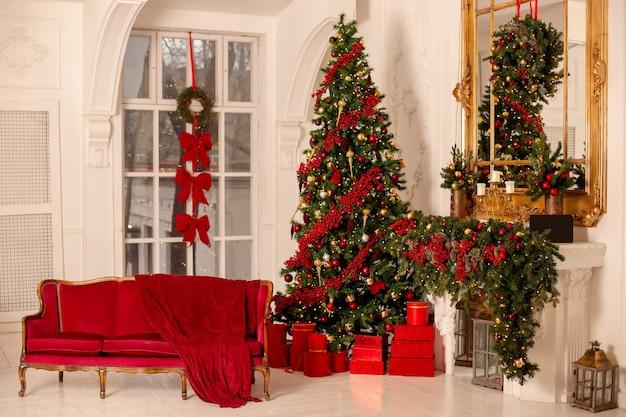 Interno rosso e oro di capodanno con un grande albero di abete rosso, un divano rosso, un camino e scatole rosse