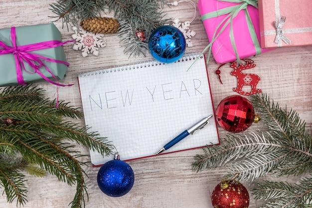 Risoluzioni per il nuovo anno nel blocco note con palline colorate e scatole regalo su un tavolo di legno