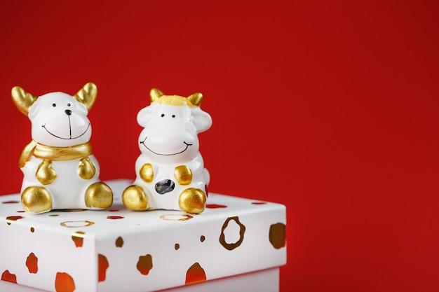 Giocattolo di capodanno di un toro e una mucca con un regalo su uno sfondo rosso