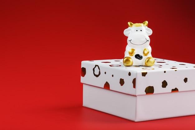 Giocattolo di capodanno di una mucca su una scatola con un regalo su uno sfondo rosso