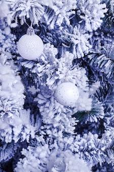 Giocattoli di capodanno su un albero di natale artificiale. palle o sfere sui rami di abete rosso ricoperti di neve. tonificante blu