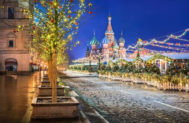 Alberi di capodanno a palline vicino al gum sulla piazza rossa di mosca e alla cattedrale di san basilio alla luce delle luci festive notturne