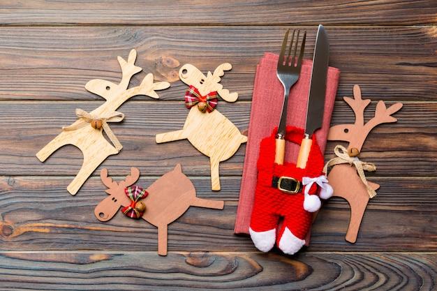 Nuovo anno set di forchetta e coltello sul tovagliolo, vista dall'alto di decorazioni natalizie e renne su legno, close up del concetto di vacanza in famiglia cena