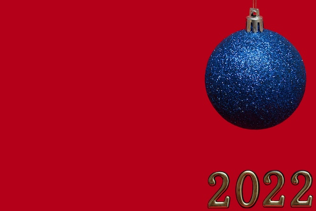 Modello blu brillante della palla del nuovo anno isolato su fondo rosso con i numeri dorati. il nuovo anno 2022 sta arrivando. layout da cartolina, confezione. banner