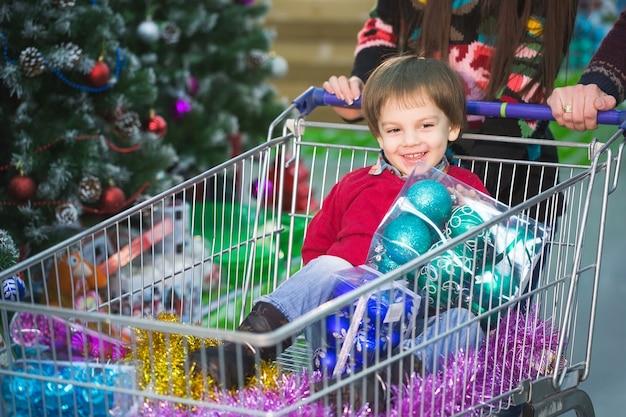 Acquisti di capodanno. un bambino fa la spesa al supermercato con i suoi genitori.