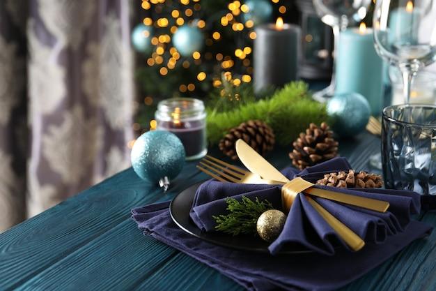 Regolazione della tavola del nuovo anno con bokeh sulla tavola di legno.