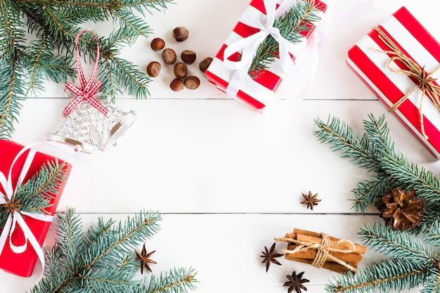 Fondo di legno del nuovo anno con rami di abete, stelle di anice, bastoncini di cannella, regali in confezione festiva con una copia dello spazio.