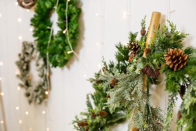 Una ghirlanda di capodanno dai rami di un albero di natale è appesa al muro. decorazioni in casa per il nuovo anno. arredare la stanza per le vacanze di capodanno
