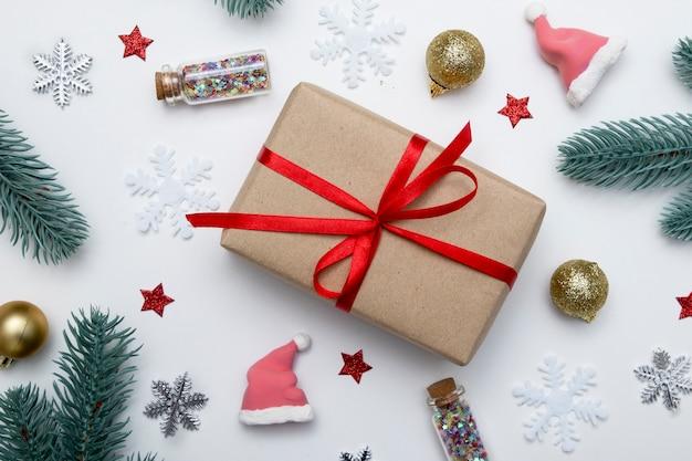 Piatto di natale di capodanno giaceva con regalo, stelle, fiocchi di neve e decorazioni per le vacanze su sfondo bianco