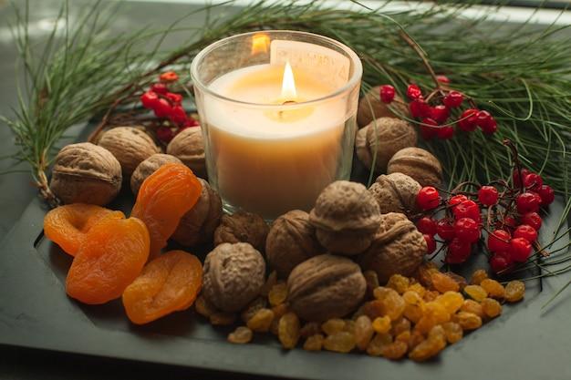Composizione di candele di capodanno con ramo di abete e pasto sano. il vassoio di natale ha servito noci di candela