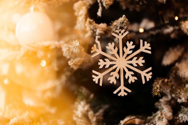 Fiocco di neve decorativo di capodanno appeso a un ramo di abete