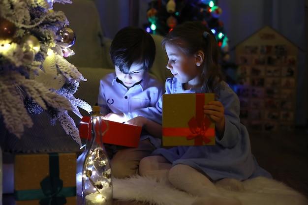 Vigilia di capodanno. la casa è decorata per le vacanze. albero di natale elegantemente vestito con una ghirlanda e una famiglia con regali e una sorpresa.