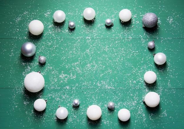 Le palle bianche e grigie di capodanno si trovano su uno sfondo di legno verde con neve