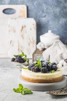 New york cheesecake o classica cheesecake con frutti di bosco freschi su pietra grigia