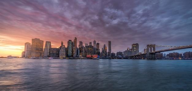 Riflessione dell'orizzonte di new york sul fiume hudson al ponte di brooklyn al tramonto