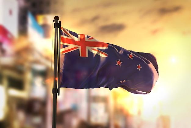 Bandiera della nuova zelanda contro la città sfocata di sfondo al retroilluminazione di alba