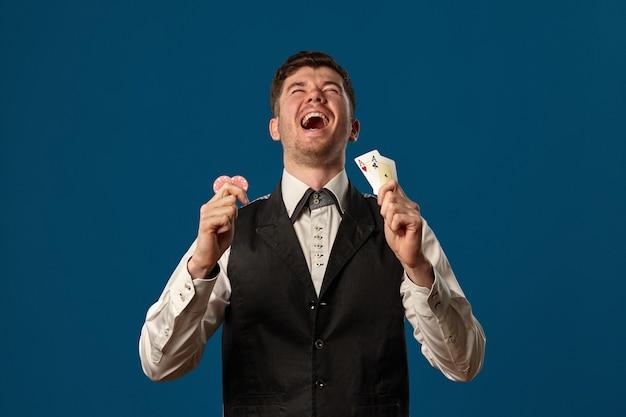Principiante nel poker in canottiera nera e camicia bianca con in mano due fiche rosse e assi in posa contro il ba...