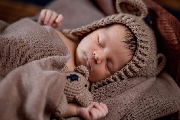 Neonato, bellissimo neonato si trova e tiene un piccolo orsacchiotto nel letto su fondo in legno.