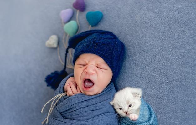 Neonato avvolto in tessuto blu e con indosso un cappello che dorme con un gattino