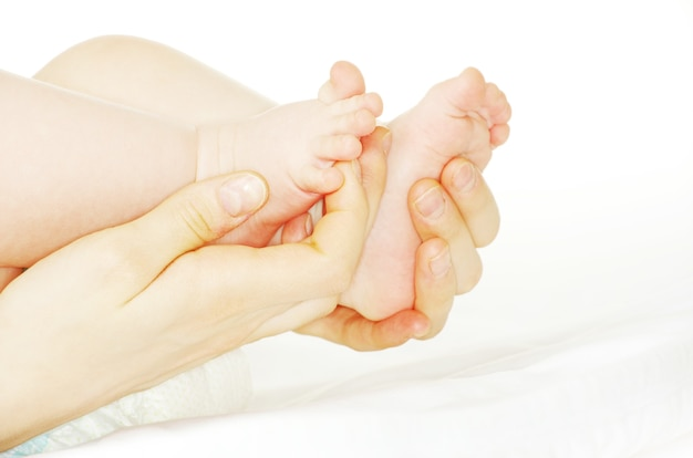 Piedi e mani del neonato isolati su bianco