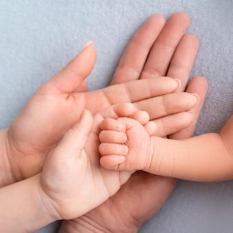 Mano del neonato. famiglia, mamma, papà e un bambino più grande tengono il pugno di un neonato. foto di alta qualità