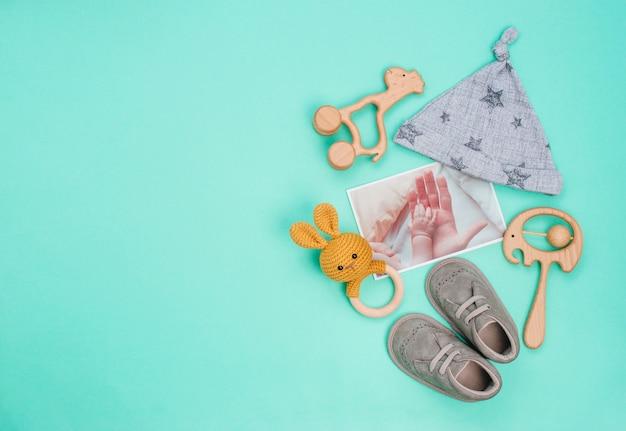 Cappello, scarpe e giocattoli del neonato sul turchese
