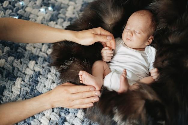Il neonato tiene il dito della madre mentre dorme