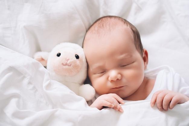 Neonato di una settimana che dorme pacificamente con un simpatico peluche nella culla in uno sfondo di stoffa