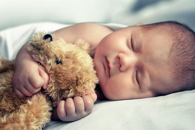 Il neonato dorme e abbraccia l'orsacchiotto